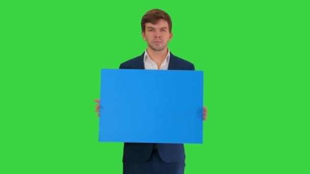 Fiatal üzletember, üres táblával a kezében, kamerát néz egy zöld képernyőn, Chroma Key.