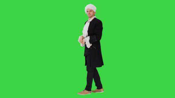 Ein als Höfling verkleideter Mann, der nichts tut und auf einem Green Screen mit Händen winkt, Chroma Key.