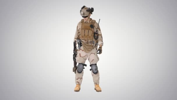 Marine standing and checking his uniform on gradient background.