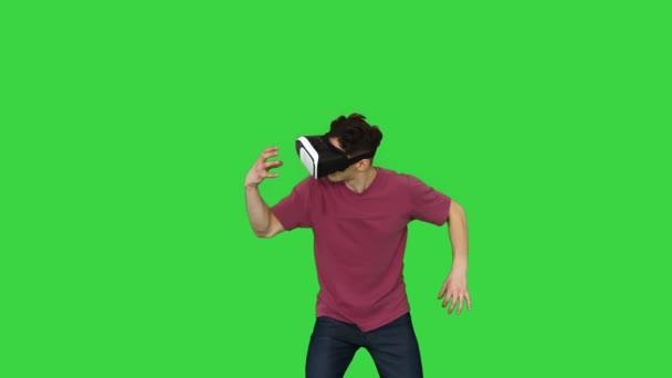 Lenyűgöző férfi VR fejhallgató szemüveggel megérinti és kölcsönhatásba lép a virtuális valóság világával egy zöld képernyőn, Chroma Key.