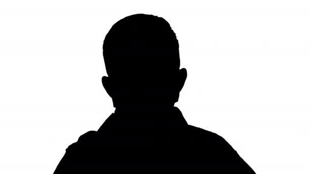 Silhouette Kleiner Junge justiert seine Gesichtsmaske und schaut in die Kamera.