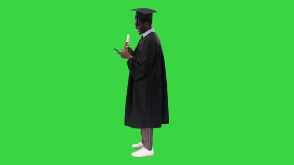 Mosolygó afro-amerikai férfi diák ballagási köntösben diplomával sms a telefonon egy zöld képernyőn, Chroma Key.