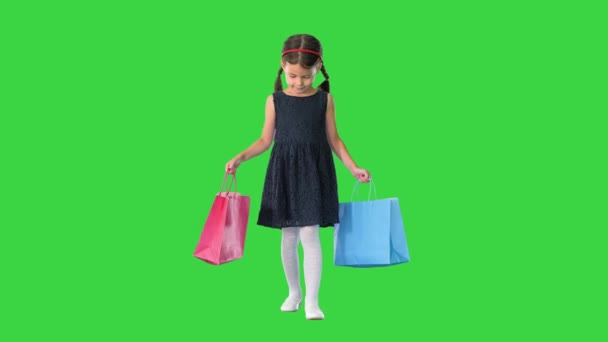 Beautiful little girl in black dress walking with shopping bags on a Green Screen, Chroma Key.