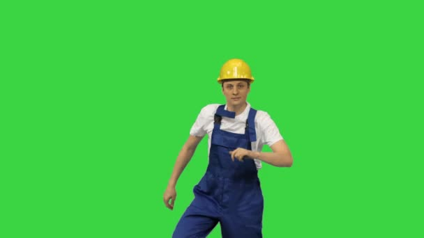 Young construction worker in yellow hardhat break dancing looking at camera on a Green Screen, Chroma Key.