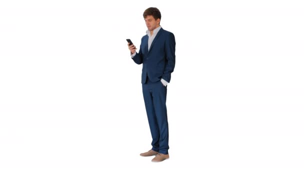 Serious businessman looking at his phone on white background.