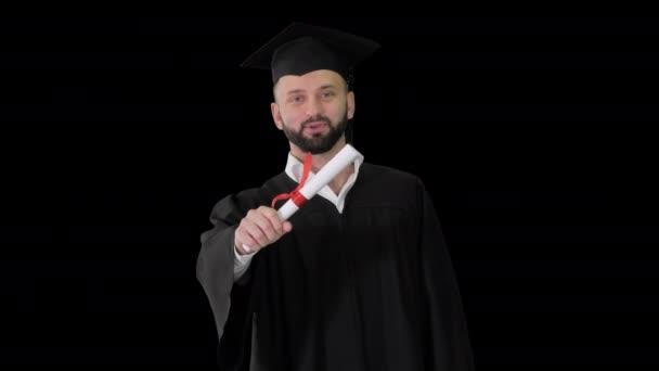 Šťastný mladý muž v maturitní čepici držící diplom a mluvící, Alpha Channel