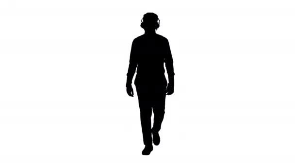 Silueta Mladý africký Američan poslouchá hudbu ve sluchátkách při chůzi.