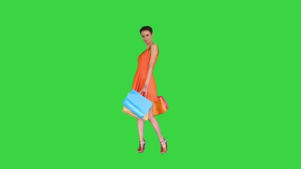 Krásná dívka ukazuje tašky s nákupy otáčející se na zelené obrazovce, Chroma Key.