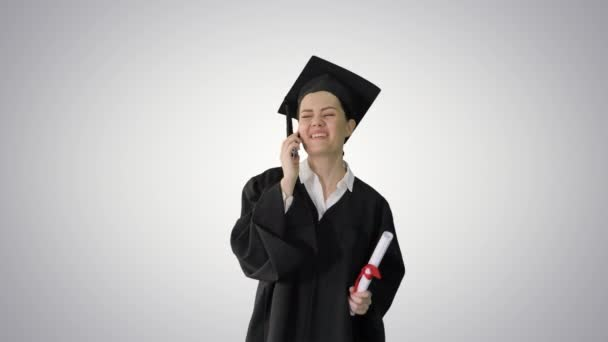 Happy female student in graduation robe talking emotionally on the phone while walking with diploma on gradient background.