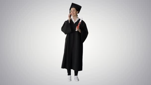 Emocionální studentka v maturitním županu mluví po telefonu drží diplom na gradientu pozadí.