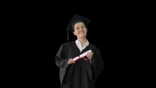 Boldog női diák ballagási köntösben sétál és éljenzik a diplomájával, Alpha Channel