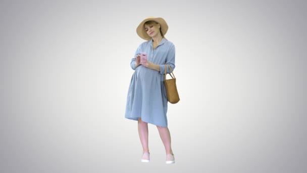Happy pregnant woman in blue dress and hat using her smartphone on gradient background.