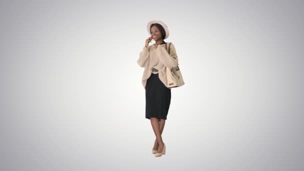 Usmívající se africká americká žena v pletené oblečení a klobouk mluví na telefonu na sklonu pozadí.
