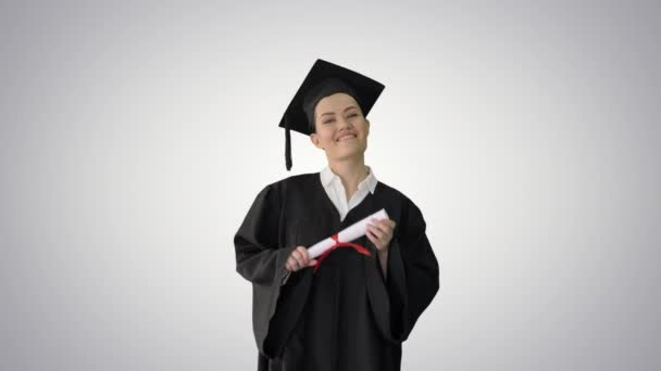 Happy female student in graduation robe walking and cheering with her diploma on gradient background.