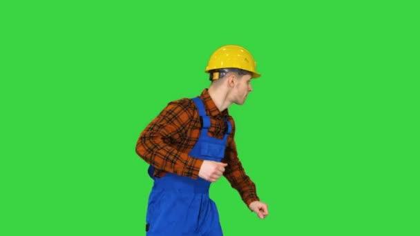 Mladý stavební pracovník v klobouku tanec hip-hop na zelené obrazovce, Chroma Key.