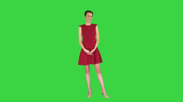 Elegant young woman agrees with someone and smiling to camera on a Green Screen, Chroma Key.
