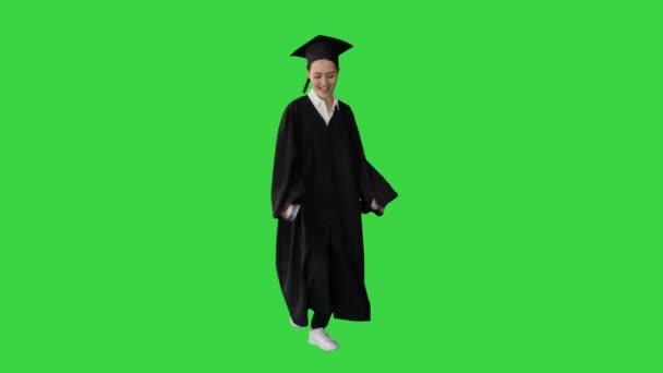 Mladý absolvent žena tanec a baví při chůzi na zelené obrazovce, Chroma Key.