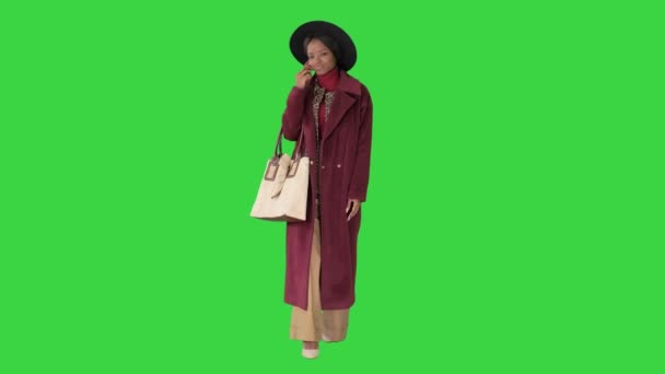 Afričanky americká módní dívka v kabátě a černý klobouk mluví do telefonu při chůzi na zelené obrazovce, Chroma Key.