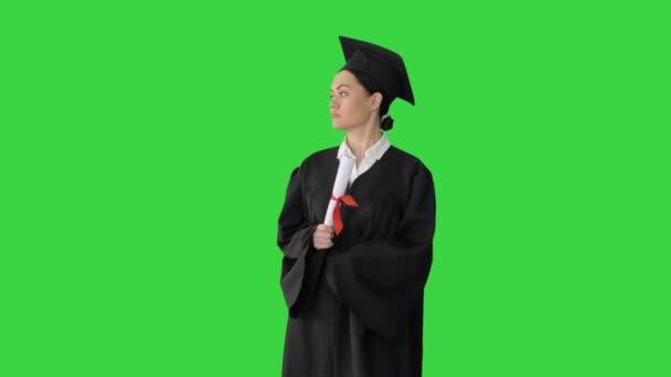 Ženské studentky v maturitním županu držící diplom a vzdávající se ho na zelené obrazovce, Chroma Key.