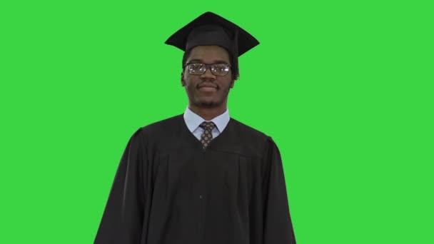 African american male student in graduation robe folding arms with diploma looking with a big smile at camera on a Green Screen, Chroma Key.