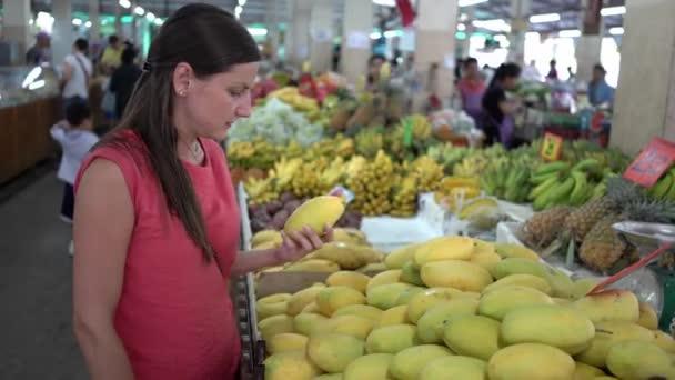 Girl choosing fresh fruit in the market. Mango close up.