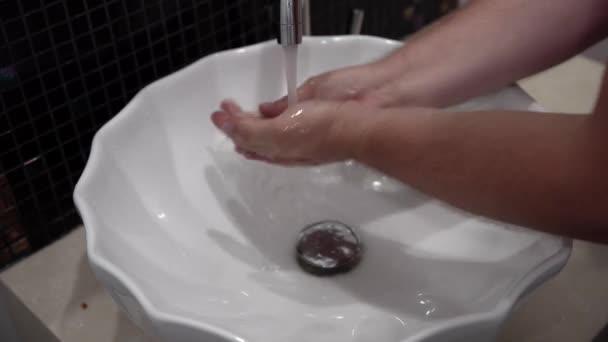 Vértes ember kézmosás szappannal a csapot. A víz a fürdőszobában.
