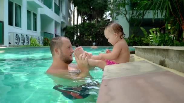 Roztomilý malý kluk a jeho otec s lekcí plavání v bazénu. Otec a dcera šťastně usmívá a hraní. Dívka, která skočila k tátovi v náručí