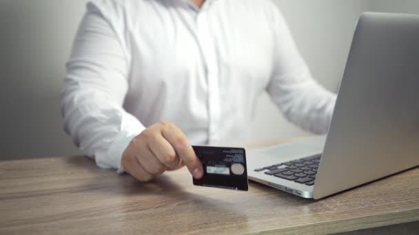 Shopping Online-Konzept. Mann hält Kreditkarte in der Hand und benutzt Laptop. männliche Hand klopft die Karte auf den Tisch