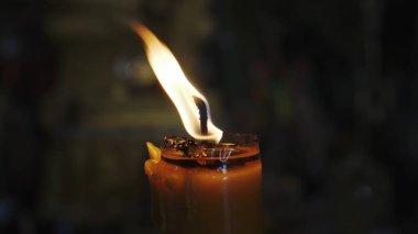 Burning candle on a black background. One burning candle on a black background.