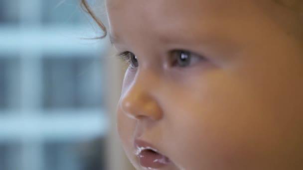 Porträt eines schönen blonden kleinen Mädchens Kind beim Anschauen des Fernsehers. Konzept: Entspannung, Glück, Familie, Überraschung