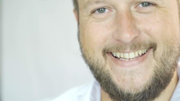Pohledný běloch s bradkou usmívající se na bílém pozadí, Portrét muže napůl tváře.
