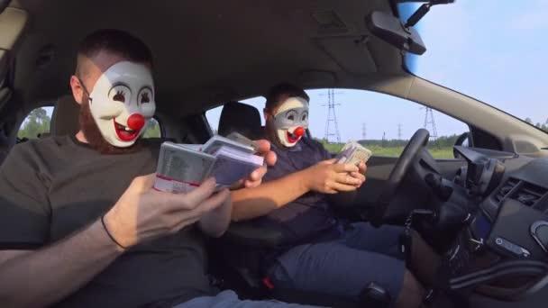 Zwei Männer in lustigen Masken mit Schusswaffen im Auto freuen sich nach einem Raubüberfall über Geld. Bewaffnete Räuber erbeuteten mit Waffen Geld.