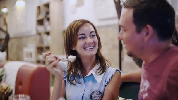 Romantic and love relationships. young couple on a date. A woman feeds her man a delicious dessert. Couple laughing in a restaurant in the evening.