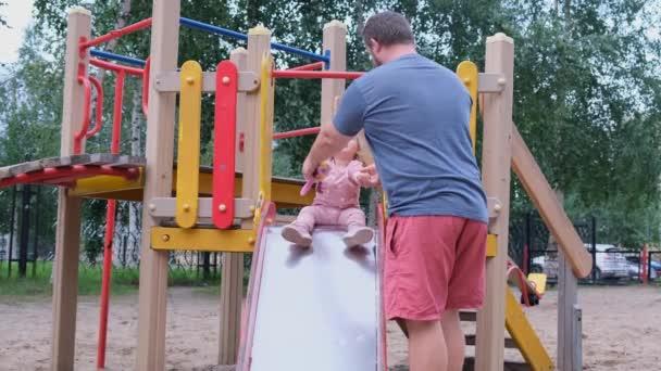 Vater und Tochter spielen auf dem Spielplatz, ein Mann fängt eine Tochter, die von einer Kinderrutsche herunterfällt.