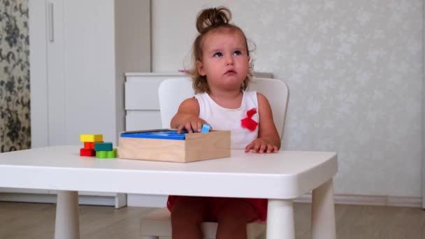 kis unatkozó lány, 2 éves, játszik oktatási játékok, stack és rendezi színes számok. A tanulás tapasztalati koncepciók, durva, finom motoros készségek révén