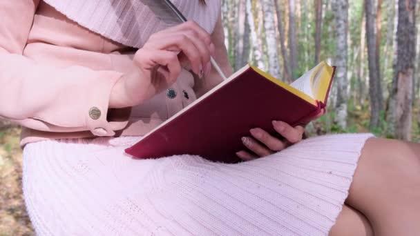 zblízka v podzimním lese, ženská ruka píše perem v knize. Žena sedí nedaleko stromu v podzimním lese a drží v rukou knihu.