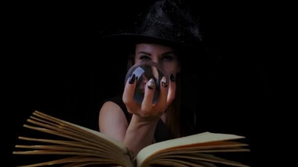 schöne sexy Frau in einem schwarzen Hexenkostüm und Hut, hält eine transparente Zauberkugel in ihren Händen und zaubert. Nahaufnahme. Halloween-Party.