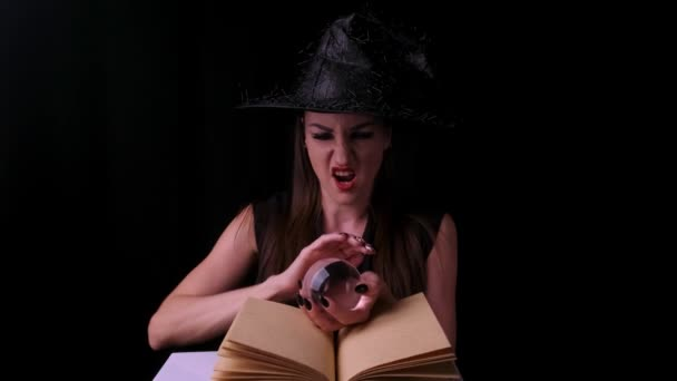 sexy Frau in schwarzem Hexenkostüm und Hut, hält eine transparente Zauberkugel in den Händen und zaubert. Halloween-Party.