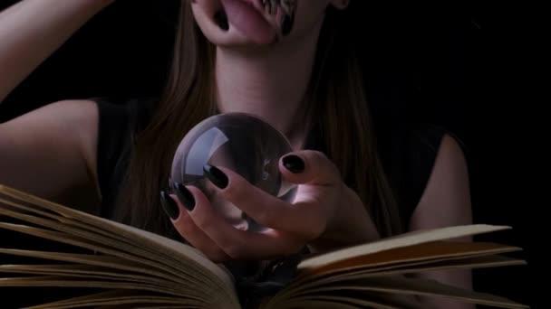 Frau in schwarzem Hexenkostüm und Hut, hält in ihren Händen eine transparente Zauberkugel über einem Buch und zaubert. Nahaufnahme. Halloween-Party.