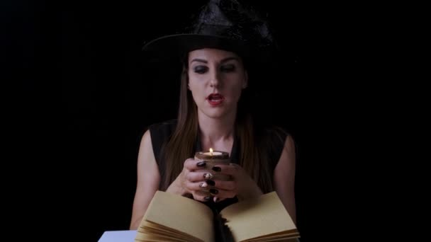 Beautiful sexy woman in a black witch costume and hat, holds a candle in her hands and conjures. Halloween holiday party.