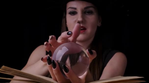 beautiful sexy woman in a black witch costume and hat, holds a transparent magic ball in her hands and conjures. close-up. Halloween holiday party.