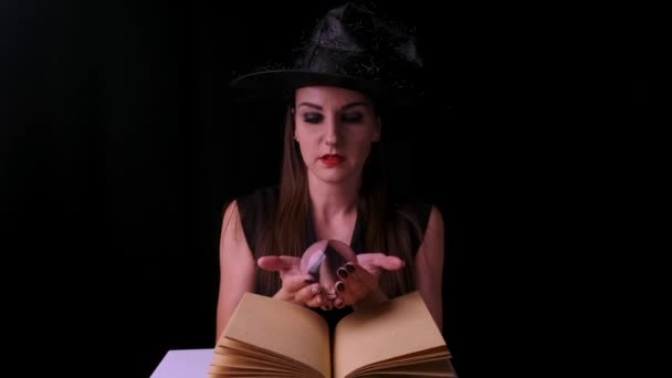 beautiful woman in a black witch costume and hat, holds a transparent magic ball in her hands and conjures. Halloween holiday party.
