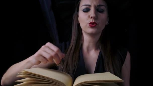 schöne sexy Frau in einem schwarzen Hexenkostüm und Hut zaubert über ein Buch mit einer Feder. Halloween-Party.