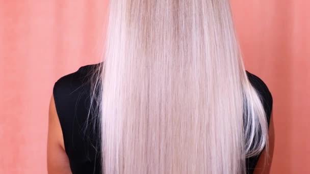Krásná žena luxusní dlouhé rovné blond vlasy. Barvené vlnité bílé blond vlasy pozadí, barvení, prodloužení, léčba, léčba koncepce. Péče o vlasy. Zpomalit 4K UHD video