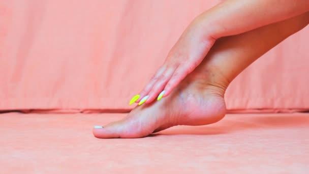 Weibchen streichelt die weiche Haut des Fußes. Die Hand eines schönen und eleganten gepflegten Mädchens berührt ihr Bein. Wellness, Peeling und Fußpflege.