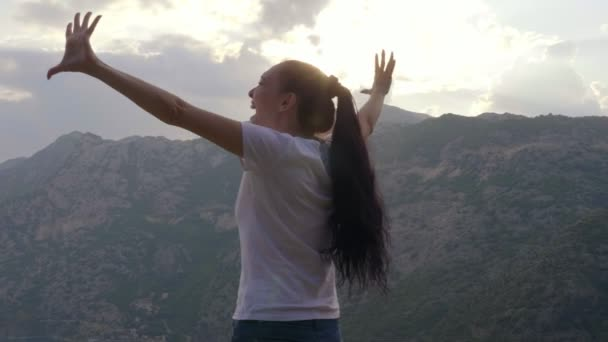 The girl screams with happiness on top of the mountain