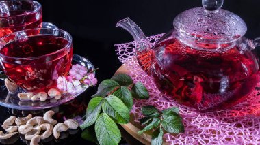 Green tea leaves or leaves of medicinal herbs lie on the table with a teapot and mugs of red tea, cashew nuts and clove flowers. Tea parties, tea traditions and ceremonies. Zen traditions of the East