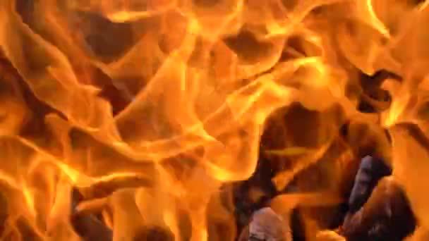 Zeitlupenvideo von Feuer und Flammen.Eine Feuerstelle, brennendes Gas oder Benzin brennt mit Feuer und Flammen.Flammen und brennende Funken in Großaufnahme, Feuermuster. Ein höllischer Feuerschein im Dunkeln mit Kopierraum