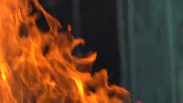 Zpomalené video ohně a plamenů.Ohniště, hořící plyn nebo benzin hoří ohněm a plameny.Plameny a hořící jiskry zblízka, požární vzory. Pekelná záře ohně ve tmě s kopírovacím prostorem