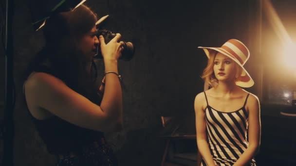 Fotograf fotografiert ein weibliches Fotomodell in einem Studio